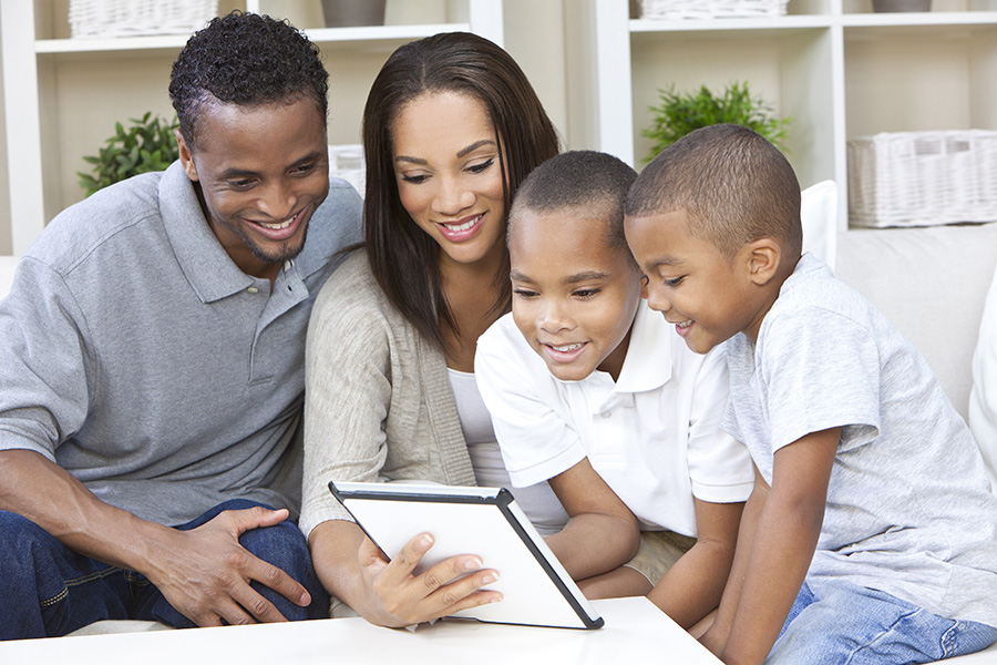 Parents and two sons, having fun using a tablet computer together at home